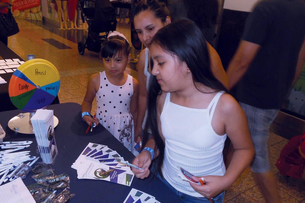 La señora Hernández y sus dos hijas son atendidas en uno de los puestos de la Feria de regreso a clases, de Cox y el Distrito Escolar del Condado Clark. | Foto Valdemar González/ El Tiempo.