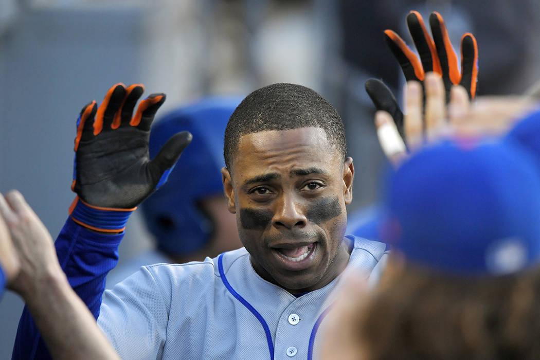 Curtis Granderson de los Mets de Nueva York es felicitado por sus compañeros de equipo después de golpear un jonrón en solitario durante la primera entrada del partido de béisbol del equipo co ...