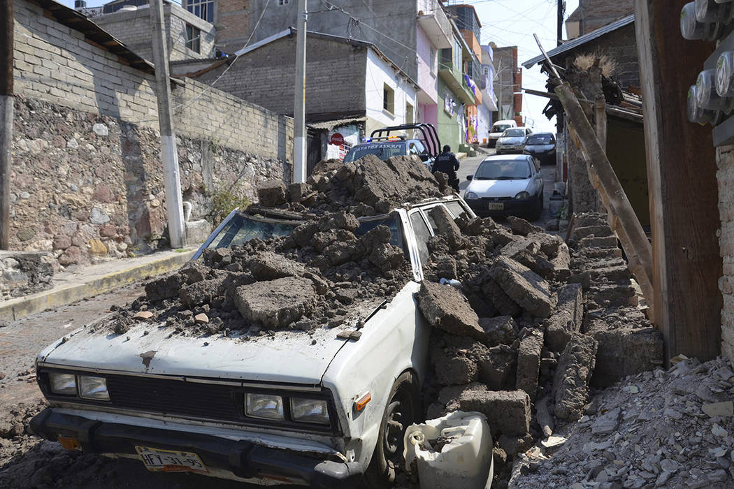 En esta foto del 18 de abril de 2014, un automóvil estacionado sufrió daños cuando un muro de adobe se derrumbó sobre él después de un fuerte terremoto sacudió Chilpancingo, México. Un pod ...