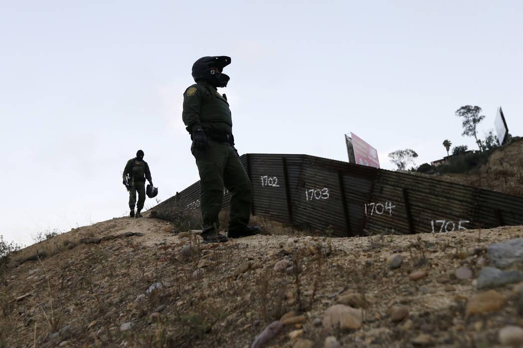 ARCHIVO - En este miércoles, 22 de junio de 2016, foto de archivo, los agentes de la Patrulla Fronteriza miran la cerca primaria que separa Tijuana, México, a la derecha, y San Diego en San Dieg ...