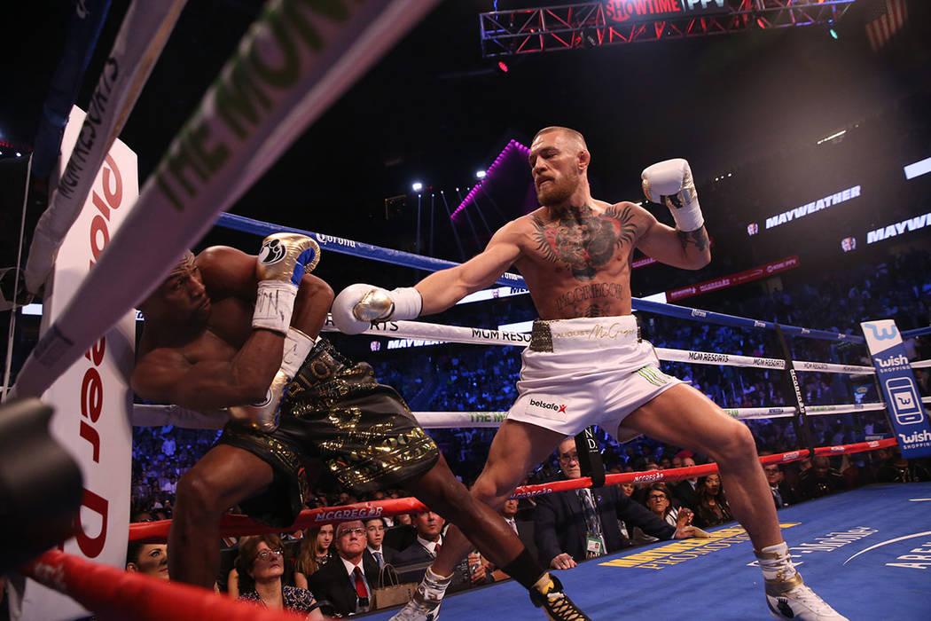 loyd Mayweather Jr., a la izquierda, se inclina para evitar un golpe de Conor McGregor durante la primera ronda de su pelea en T-Mobile Arena, el sábado 26 de agosto de 2017, en Las Vegas.| Foto  ...