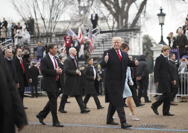 El Presidente Donald Trump saluda a la gente, mientras camina acompañado de su esposa Melania y su hijo Barron en el desfile inaugural en Washington, en enero 20 del 2017. (Carlos Barria/Reuters).
