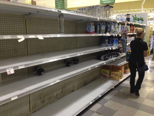 Un consumidor pasa por los estantes donde normalmente hay botellas de agua, pero ahora están vacías luego de la compra masiva, en octubre 5 del 2016, en prevención para la llegada del huracán  ...