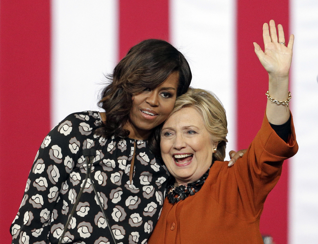 La primera dama Michelle Obama abraza a la candidata presidencial demócrata Hillary Clinton, durante un acto de campaña en Winston-Salem, N.C., el jueves 27 de octubre del 2016. (AP Photo/Chuck  ...