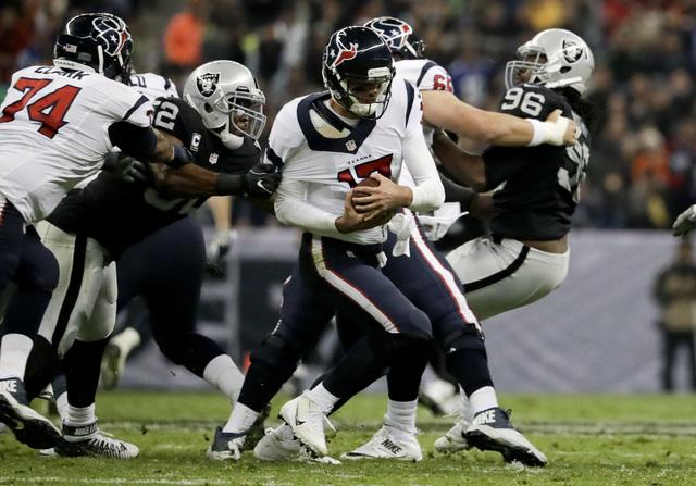 Khalil Mack (52), defensa de los Oakland Raiders sujeta por el brazo al quarterback  Brock Osweiler de los Houston Texans en la primera mitad del juego de fútbol americano de la NFL el 21 de novi ...