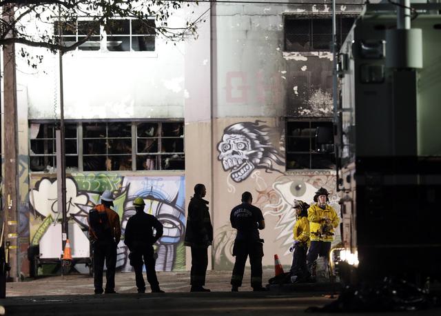 Personal de emergencia se ubica el domingo 4 de diciembre del 2016 frente a la bodega donde el pasado viernes 2 ocurrió un incendio que dejó decenas de muertos, en Oakland, California. (Marcio J ...