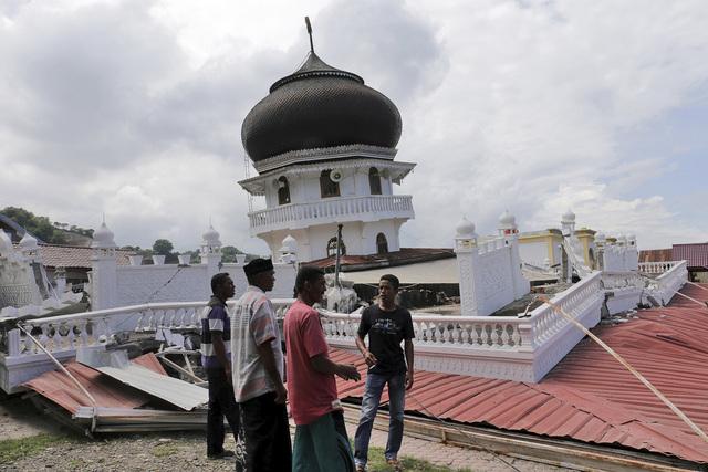 Unos hombres inspeccionan la estructura de una mesquita colapsada durante un terremoto en Pidie Jaya, Aceh provincia de Indonesia, la mañana del 7 de diciembre del 2016. (AP Photo/Heri Juanda).