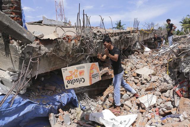 Un hombre remueve cosas de los escombros de un edificio derrumbado por un potente terremoto ocurido el miércoles 7 de diciembre del 2016 en Pidie Jaya, Aceh, provincia de Indonesia. (Heri Juanda/AP).