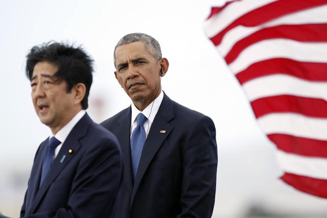 """El Presidente Barack Obama escucha al primer ministro de Japón, Shinzo Abe, mientras habla en Kilo Pier con la vista del """"USS Arizona Memorial"""", parte de World War II Valor, en el Monumento Nacio ..."""