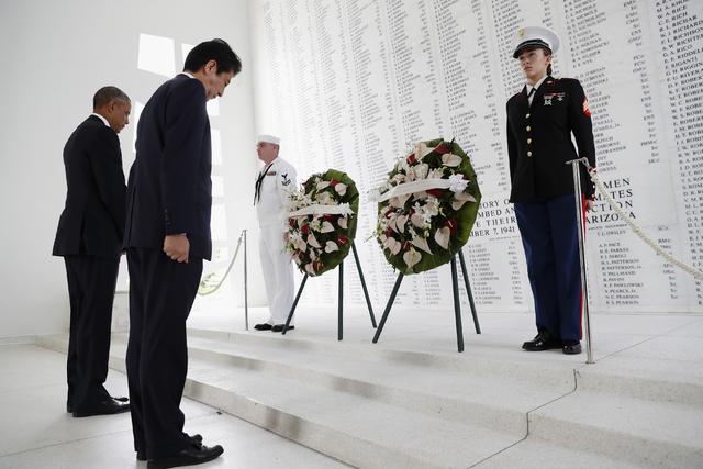 El Presidente Barack Obama, izquierda, y el primer ministro de Japón Shinzo Abe presentan sus respetos con ofrendas florales y un momento de silencio en el USS Arizona Memorial, parte de el World ...