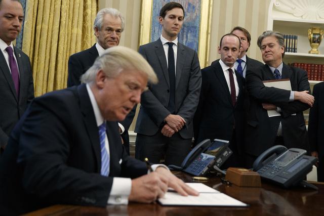 El presidente Donald Trump firma una orden ejecutiva el 23 de enero del 2017 en la Casa Blanca. Lo observan sus colaboradores cercanos, desde la izquierda: White House Chief of Staff Reince Priebu ...