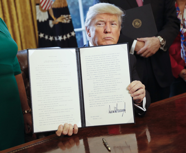 """El President Donald Trump sostiene en la Casa Blanca la orden ejecutiva que firmó el 3 de febrero del 2017, para revisar la """"Ley Dodd-Frank"""" que regula los servicios financieros luego de la crisi ..."""