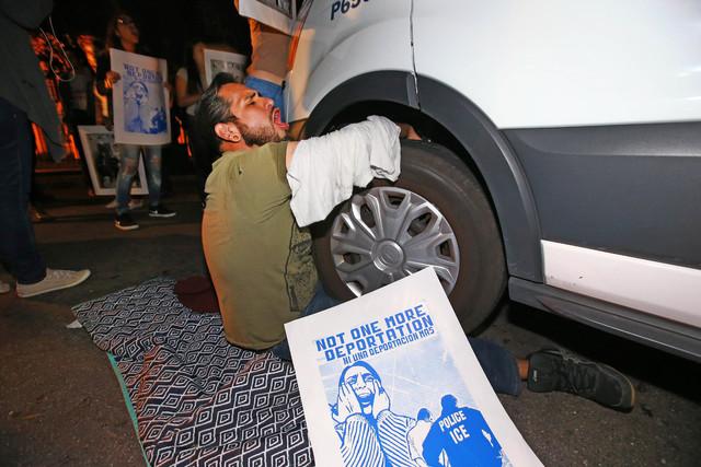 Un hombre en protesta se sujeta a la van en la que se transporta a la indocumentada Guadalupe Garcia de Rayos, el 8 de febrero del 2017, afuera de las oficinas de Immigration and Customs Enforceme ...