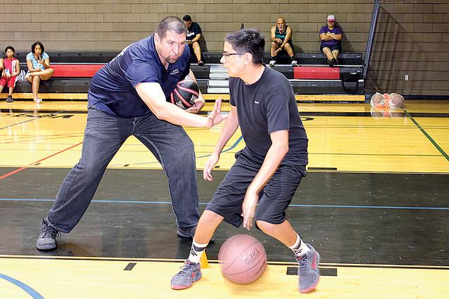 El entrenador de basquetbol, Wilmer Carvajal muestra a Ángel como defender el balón durante un partido, esto durante una clase el sábado 20 de agosto de 2016. Foto El Tiempo/Cristian De la Rosa
