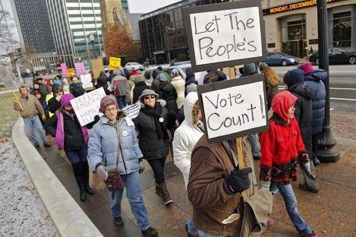 Manifestantes contra Donald Trump marchan afuera de la Legislatura de Ohio, antes que los miembros del Colegio Electoral voten, en Columbus, Ohio, el lunes 19 de diciembre del 2016. El total de lo ...