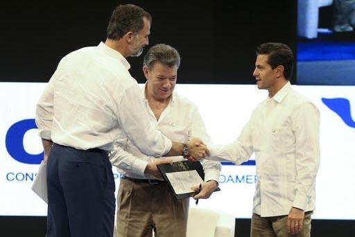 El Presidente de Colombia, Juan Manuel Santos, aparece al centro con el Rey Felipe de España (izquierda) quien saluda al presidente  de Mexico, Enrique Peña Nieto, durante un forum como parte de ...