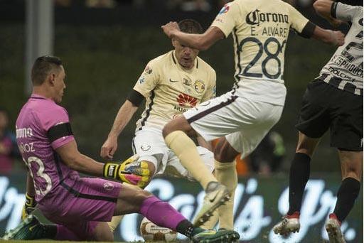 El portero del equipo America, Moises Muñoz, izquierda, respaldado por sus defensas (uniforme amarillo), bloquea el balón tirado por Edgar Espíndola, del Necaxa (uniforme oscuro) en el partido  ...