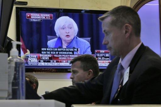 La presidenta de la Reserva Federal, Janet Yellen, aparece en una pantalla, mientras gente trabaja en  instalaciones de la Bolsa de Valores en Nueva York. Yellen informó del aumento a la tasa de  ...