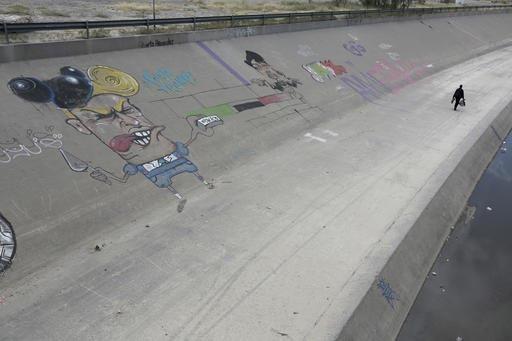 Un hombre camina el 10 de noviembre del 2016 en el lado mexicano de los límites en la frontera México - Estados Unidos, en Río Grande, Ciudad Juárez, Chihuahua, México. El graffiti es del pre ...