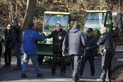 Un hombre, al centro, entrega una tarjeta a agentes mientras otro intenta conducir un tractor en la villa Upper Brookville, en el poblado de Oyster Bay, N.Y., en Long Island, el viernes 30 de dici ...