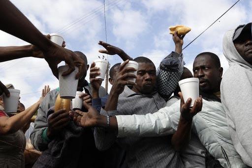 En esta foto de octubre 3 del 2016 migrantes haitianos reciben comida y bebidas de voluntarios. Los migrantes esperan en la línea fronteriza de Tijuana con Estados Unidos, para obtener una cita q ...