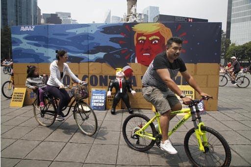 """Una familia en bicicleta pasa por un mural de cartón con la pintura de un muro, el mensaje """"Unidos contra Trump"""", y la imagen del republicano Donald Trump, y al lado una piñata con la forma del  ..."""