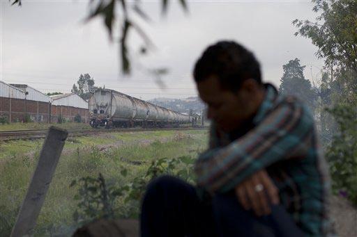 """El 30 de julio del 2014 se ve a un migrante de origen centroamericano sentado bajo un árbol en una parte de México en la ruta que sigue el tren (al fondo) entre Veracruz y """"Lechería"""", el Estado ..."""