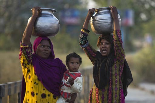 Mujeres pobres en Pakistan llevan agua en sus cabezas mientras una de ellas también carga a su bebé, el 17 de octubre del 2016, en la población de Rawalpindi, Pakistan. Ellas trabajan desde que ...