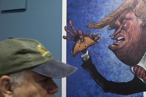 """Un turista americano pasa junto a la caricatura de Donald Trump quien está apunto de comerse un taco con un mexicano que le saca la lengua. Forma parte de la exhibición """"Trump: un muro de carica ..."""