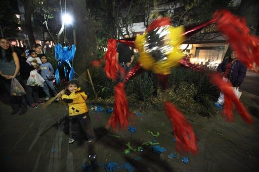 """En esta foto de archivo, de diciembre 19 del 2013, un niño trata de romper una piñata en un barrio de la Ciudad de México. Las piñatas son parte de """"Las Posadas"""", que empiezan el 16 de diciemb ..."""