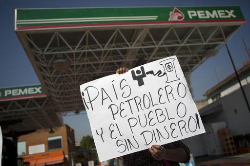 """Una mujer protesta por el incremento de los precios de los combustibles en México, con un cartel que dice: """"País petrolero y el pueblo sin dinero"""". La protesta ocurre en la calzada de Tlalpan, C ..."""