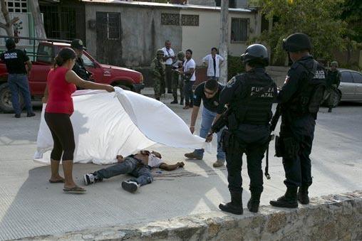 Funcionarios del servicio forense tapan el cuerpo de Alejandro Gallardo Perez, de 23 años, después que fue baleado a muerte en las afueras del Puerto de Acapulco, Guerrero, México, en abril del ...