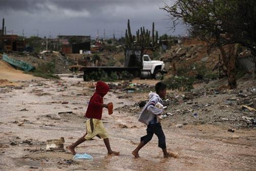 Niños de pocos recursos caminan en uno de los barrios pobres de Cabo San Lucas, Mexico, en un día de mal temporal en el 2009. (Foto Archivo/AP/Guillermo Arias).