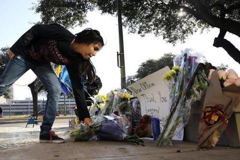 Faith Reyna deja un ramo de flores ante una ofrenda al oficial de policía Benjamin Marconi, víctima de disparos de fuego que le cobraron su vida, el domingo 20 de noviembre dle 2016 mientras imp ...