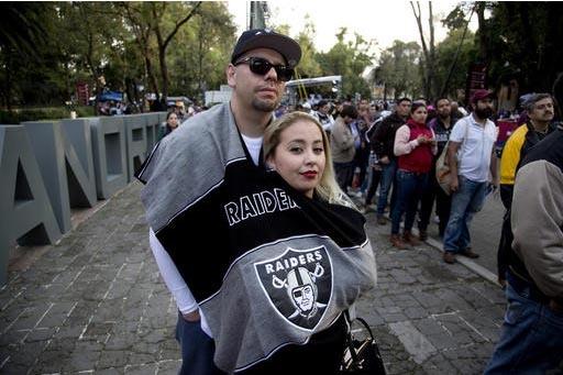 Fanáticos del equipo de fútbol americano, Raiders de Oakland, observan una sesión de autógrafos de las porristas,  durante el Fan Festival de la NFL en la ciudad de México, el 20 de noviembre ...