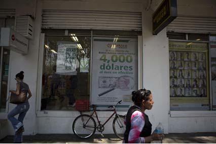 La gente pasa por un negocio de transferencias de dinero en la Ciudad de México, el 5 abril del 2016. Informes oficiales en México, a fines de octubre indican que las remesas a ese país aumenta ...