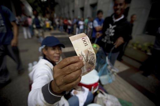 En Caracas, Venezuela, el martes 13 de diciembre del 2016, un vendedor de la calle inspecciona un billete de 100 bolívares mientras gente hace fila para cambiar sus billetes de esa denominación  ...