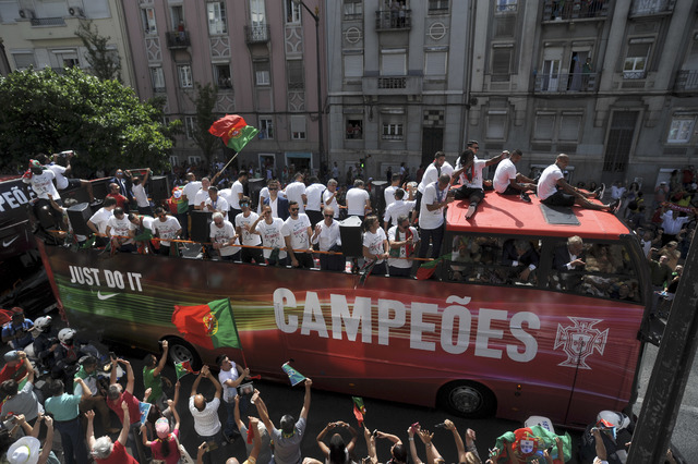Portugal's soccer team with the Euro 2016 trophy take part in a bus parade in Lisbon, Portugal, Monday, July 11, 2016. Hundreds of thousands of jubilant people lined the sunbaked streets of the Po ...