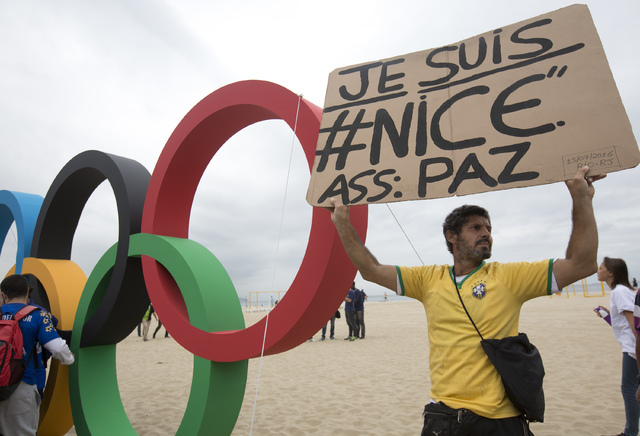 A man holds a sign to show solidarity with Nice during the presentation of Olympic rings made from recycled material, at Copacabana beach in Rio de Janeiro, Brazil, Thursday, July 21, 2016. Brazil ...