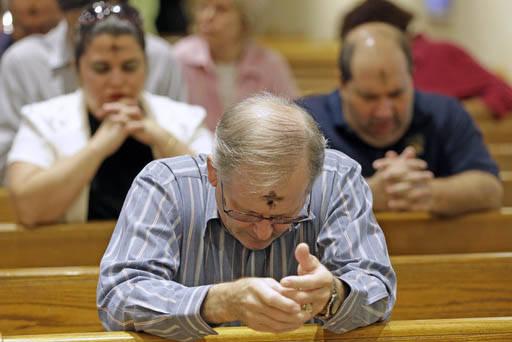 Fieles católicos rezan después de tomar la cruz de ceniza, el miércoles uno de marzo del 2017 durante un servicio religioso en un templo católico en la ciudad de Virginia Gardens, Florida. (AP ...