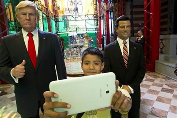 El peruano Joaquín Núñez, de 10 años, se toma una foto entre réplicas de cera del presidente estadounidense Donald Trump, izquierda, y el presidente mexicano Enrique Peña Nieto, en la entrad ...