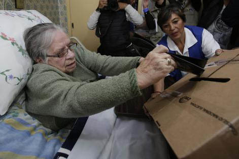 El viernes 17 de febrero Lourdes Vasquez, quien es minusválida, deposita su voto, en su casa en Quito, antes de la elección general el domingo 19 de febrero del 2017, en Ecuador. Los ecuatoriano ...