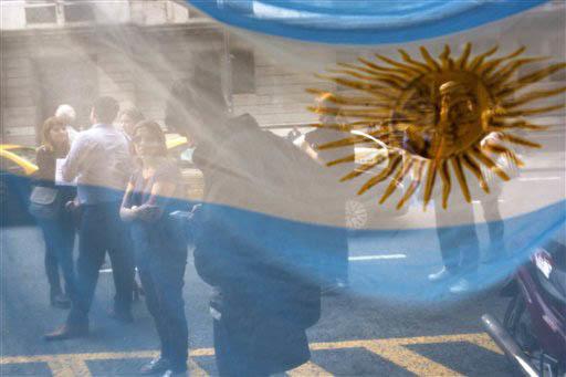 La bandera argentina deja ver detrás a gente en Buenos Aires. (Foto Archivo/AP/Rodrigo Abd).