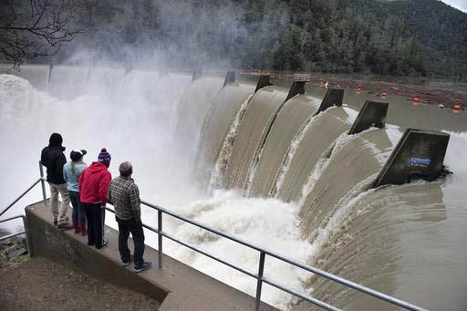 Un grupo de personas mira correr el alto volumen de agua luego de las lluvias y nevadas recientes en la presa North Fork en el lago  Clementine el 9 de enero del 2017, cerca de Auburn, Calif. (Ran ...