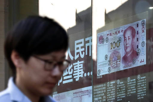 Una persona pasa junto a una ventana de banco con un cartel mostrando un billete. Las autoridades informaron el 27 de febrero del 2017 que en redadas contra operaciones bancarias ilegales y lograr ...