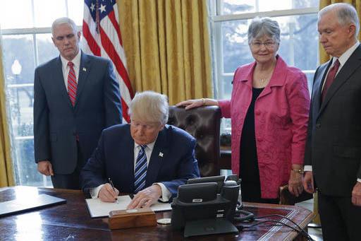 El Presidente Donald Trump firma ordenes ejecutivas para reducir el crimen. Lo acompañan el vicepresidente Mike Pence, desde la izquierda, Mary Sessions, esposa del nuevo Procurador de Justicia d ...