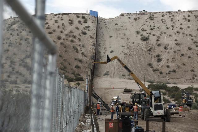 En esta foto de archivo, del 10 de noviembre del 2016, se ve a obreros que continúan trabajando en la construcción de una cerca que divide a los poblados fronterizos de Anapra, Mexico, y Sunland ...
