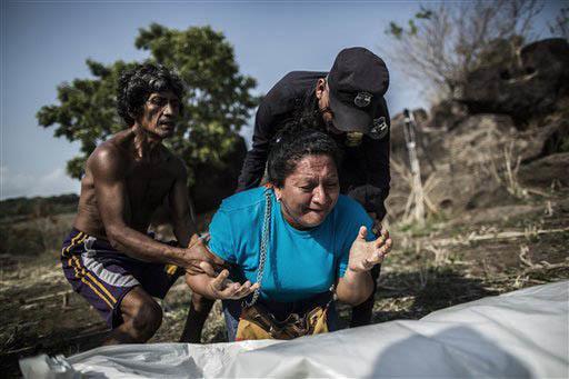 """En esta foto de archivo, del 28 de mayo del 2015, familiares se duelen por la muerte de Alberto Hernández Escalante, encontrado en una fosa clandestina en el área rural cerca de """"Caserio el Chum ..."""
