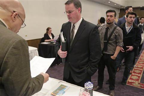 En esta foto de archivo, Abril 22, 2015, el gerente de Microtrain, atiende a personas que buscan empleo, durante una feria de empleo en Chicago. El mercado laboral del país va bien según informe ...