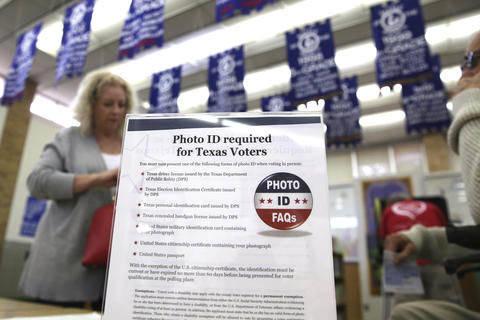 Esta foto de archivo, de Marzo 1, 2016, un letrero informa a los votantes de Texas la obligación de presentar identificación con fotografía para ejercer el ederecho, en Arlington, Texas. El 2 d ...